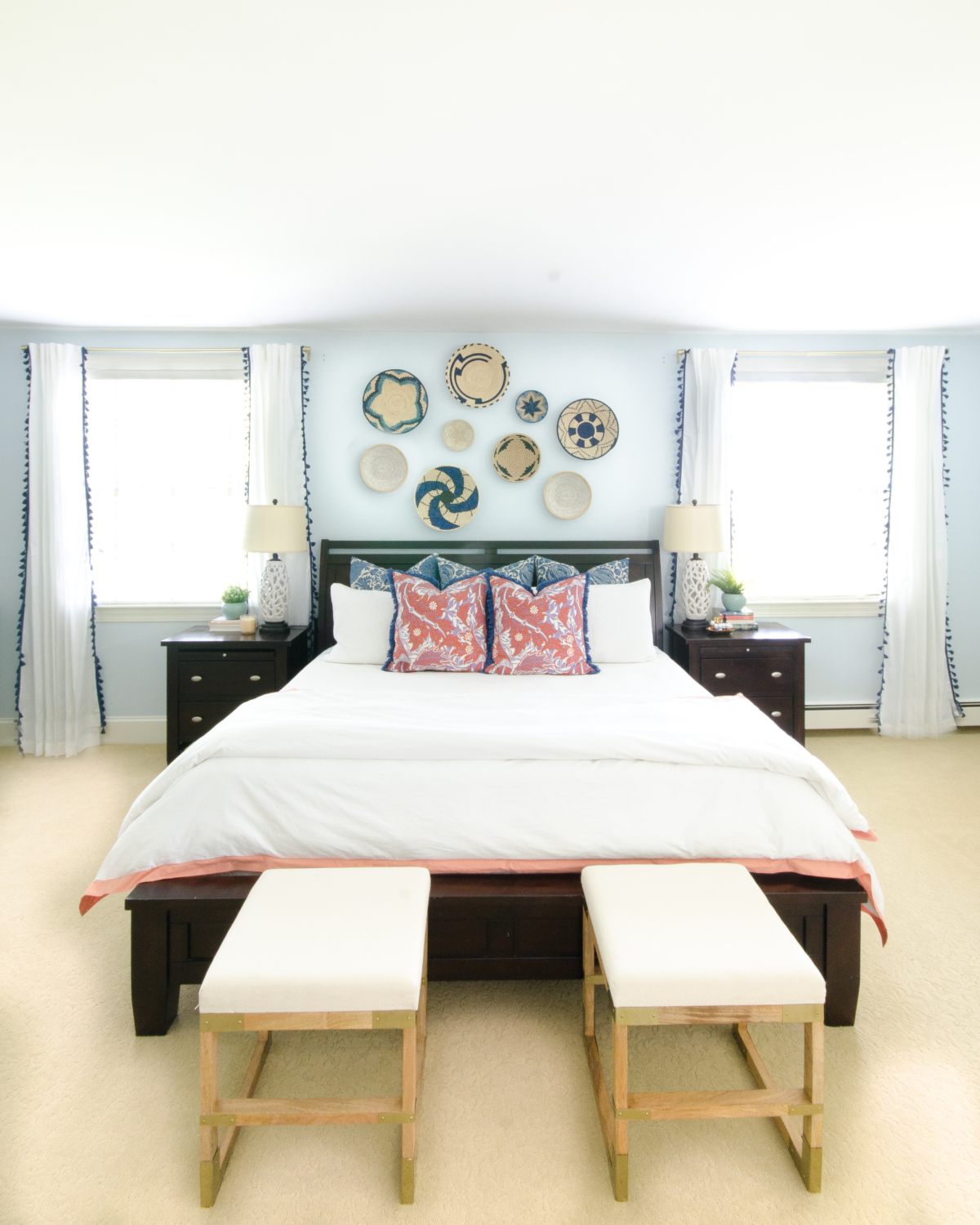 A bright, happy blue and white bedroom with pops of coral and woven basket wall art
