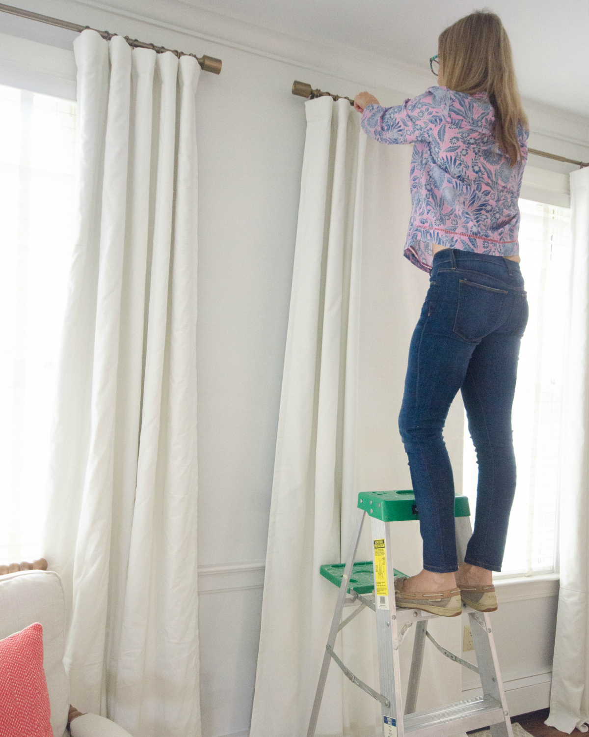 The final step in how to get your curtains to hang straight is to take some twine and loosely tie it around the bottom folds to hold them in place.