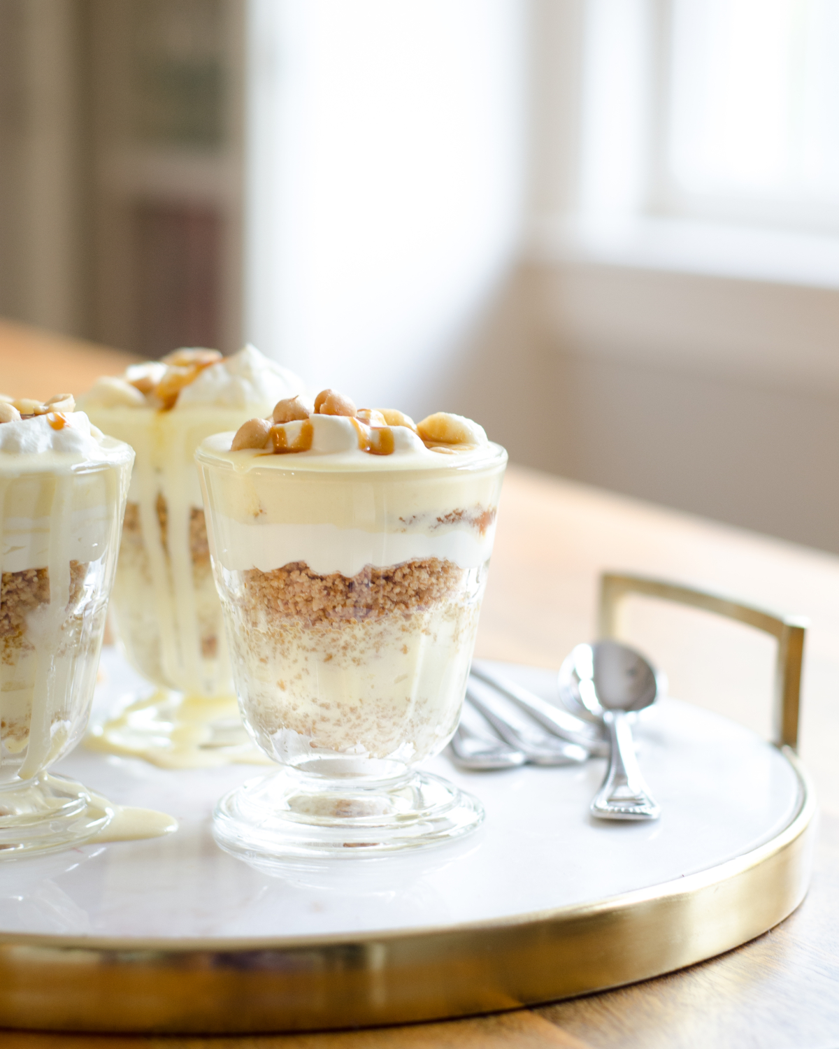 Gluten free banana cream pie recipe, in parfait form! Gorgeous individual dessert servings topped with salted caramel and peanuts for a banana cream pie like you've never tasted before!