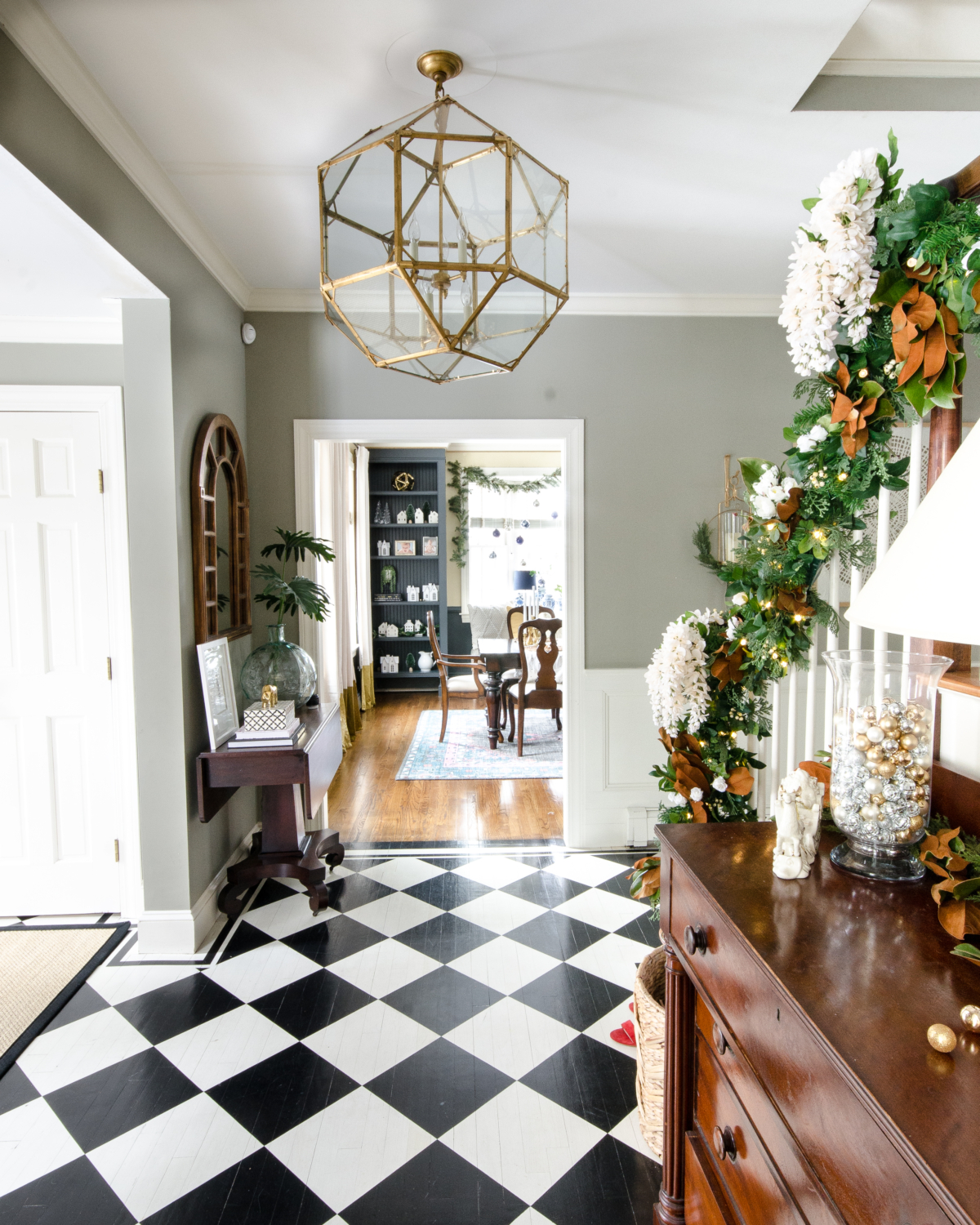 Christmas entryway with black and white checked floor, green and magnolia garland with white flowers
