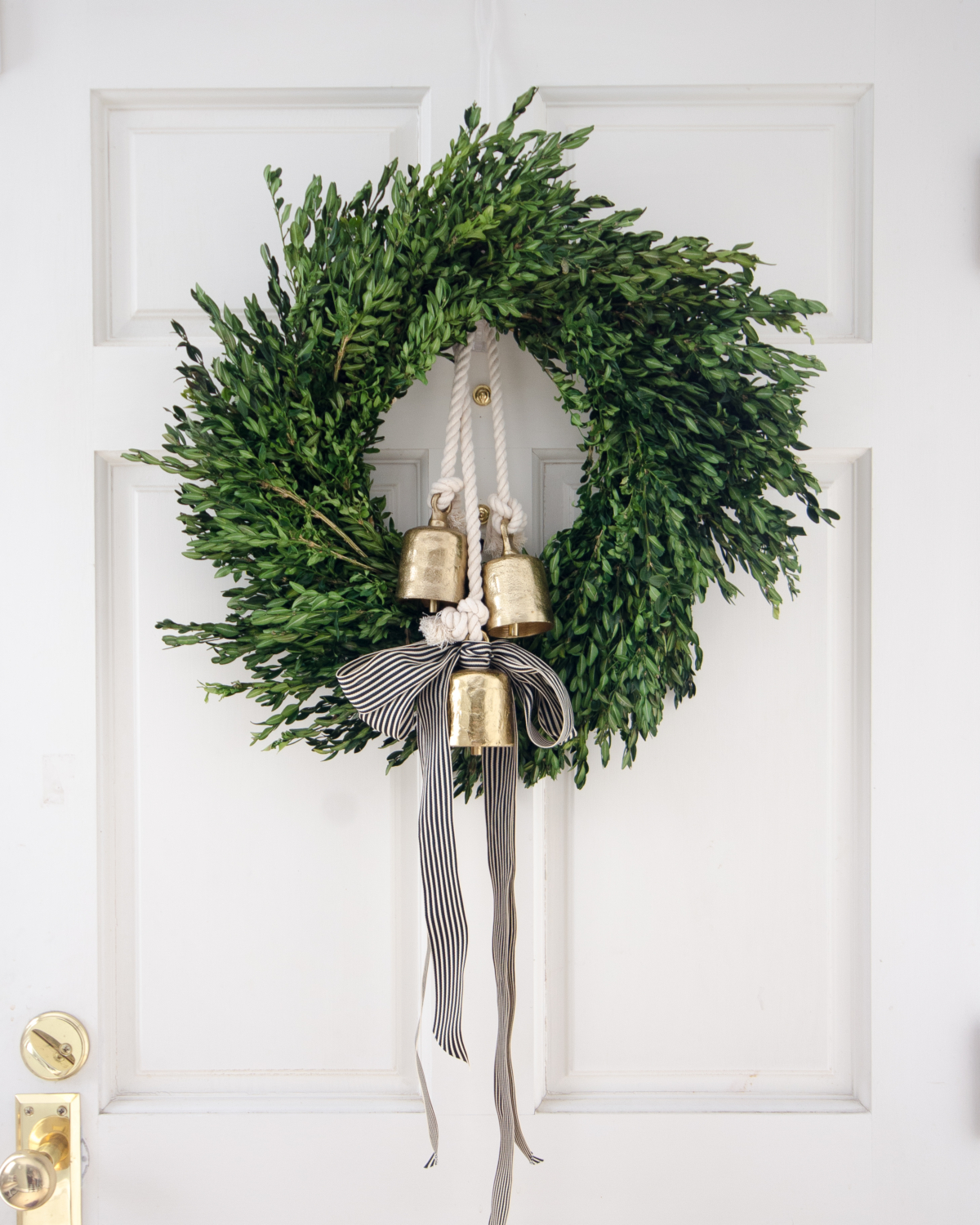 Christmas boxwood wreath, gold bells, black and white striped ribbon