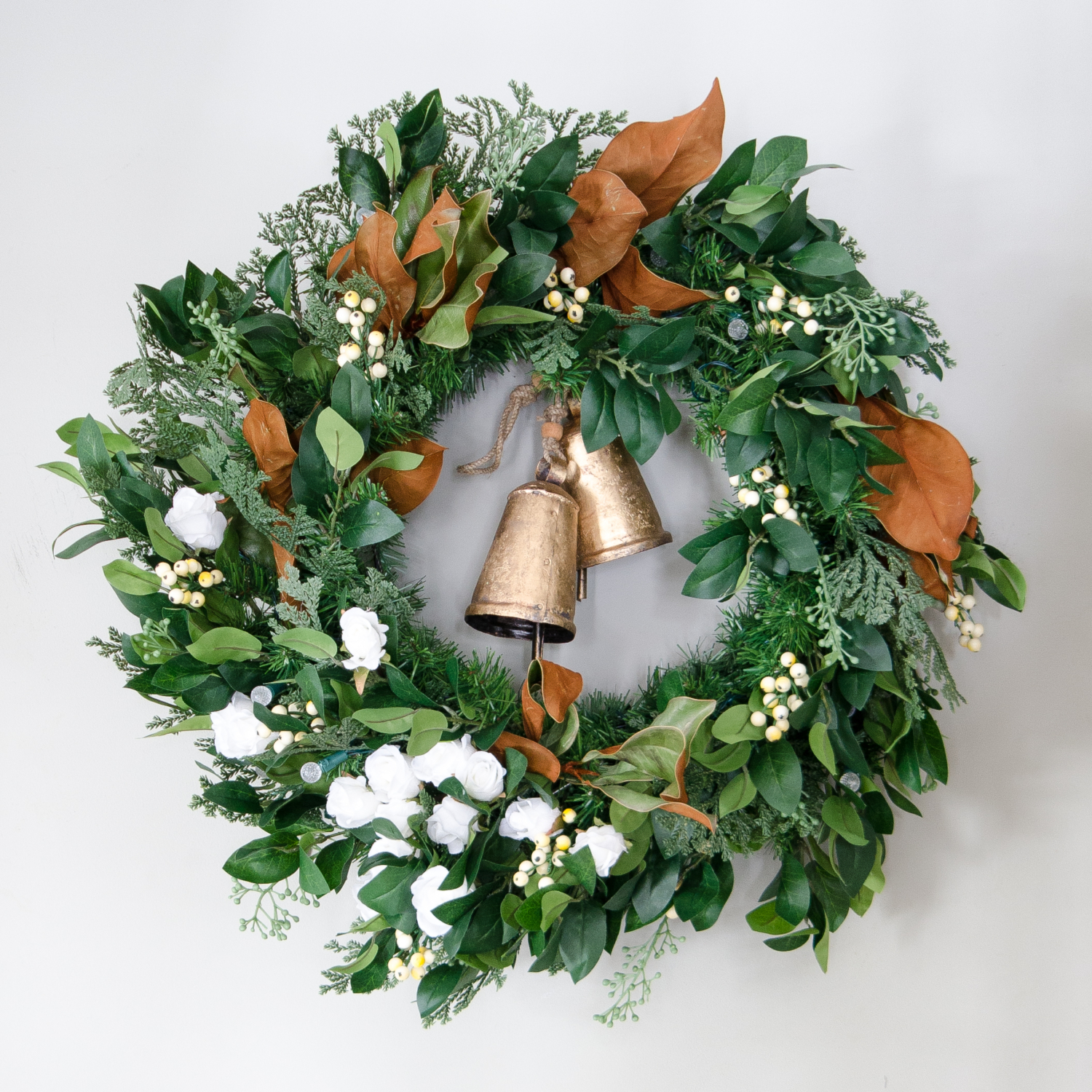 Christmas wreath with magnolia, white berries, white flowers, and gold bells