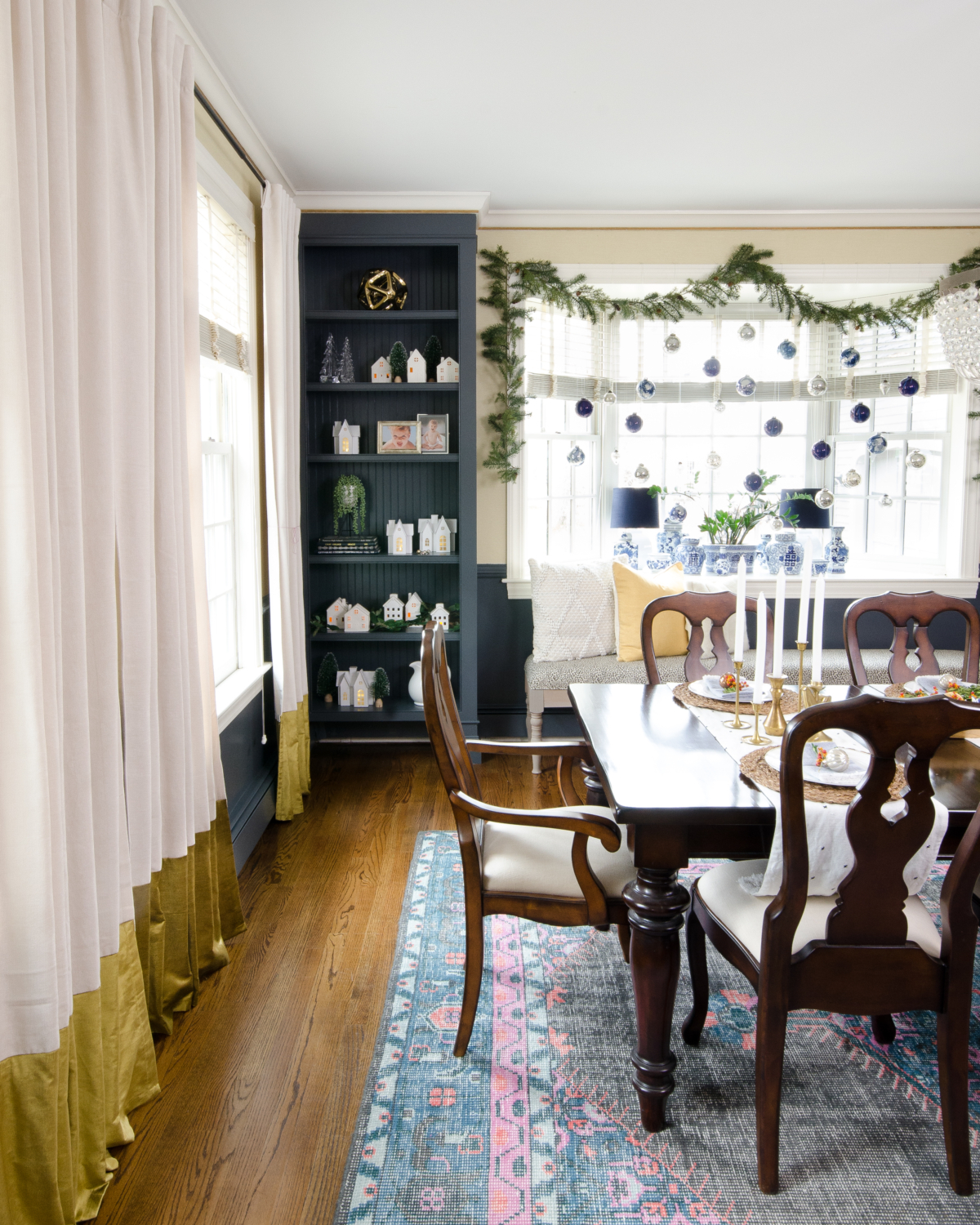 Christmas dining room with blue and white pottery, white ceramic houses, dark walls