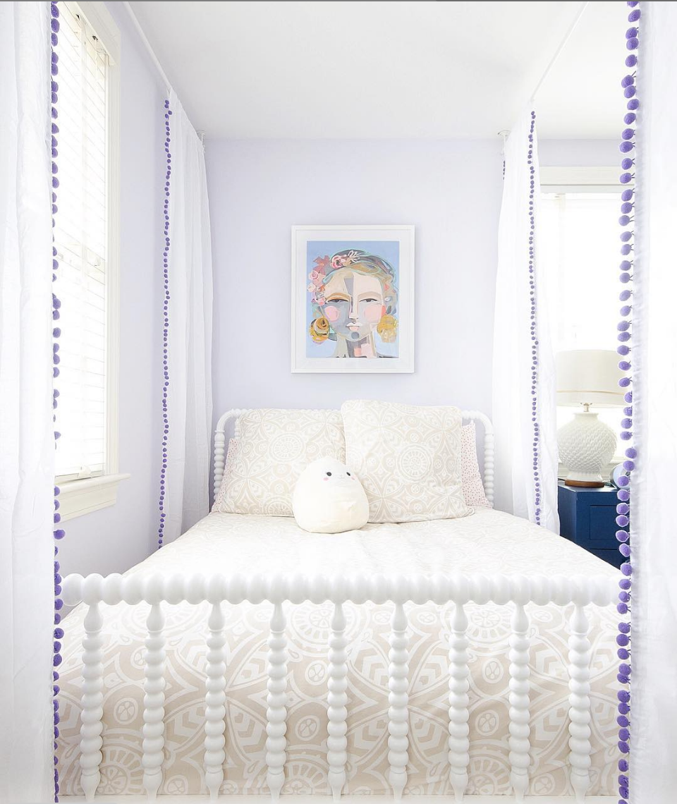Purple and white girl's bedroom with a classic Jenny Lind spindle bed.