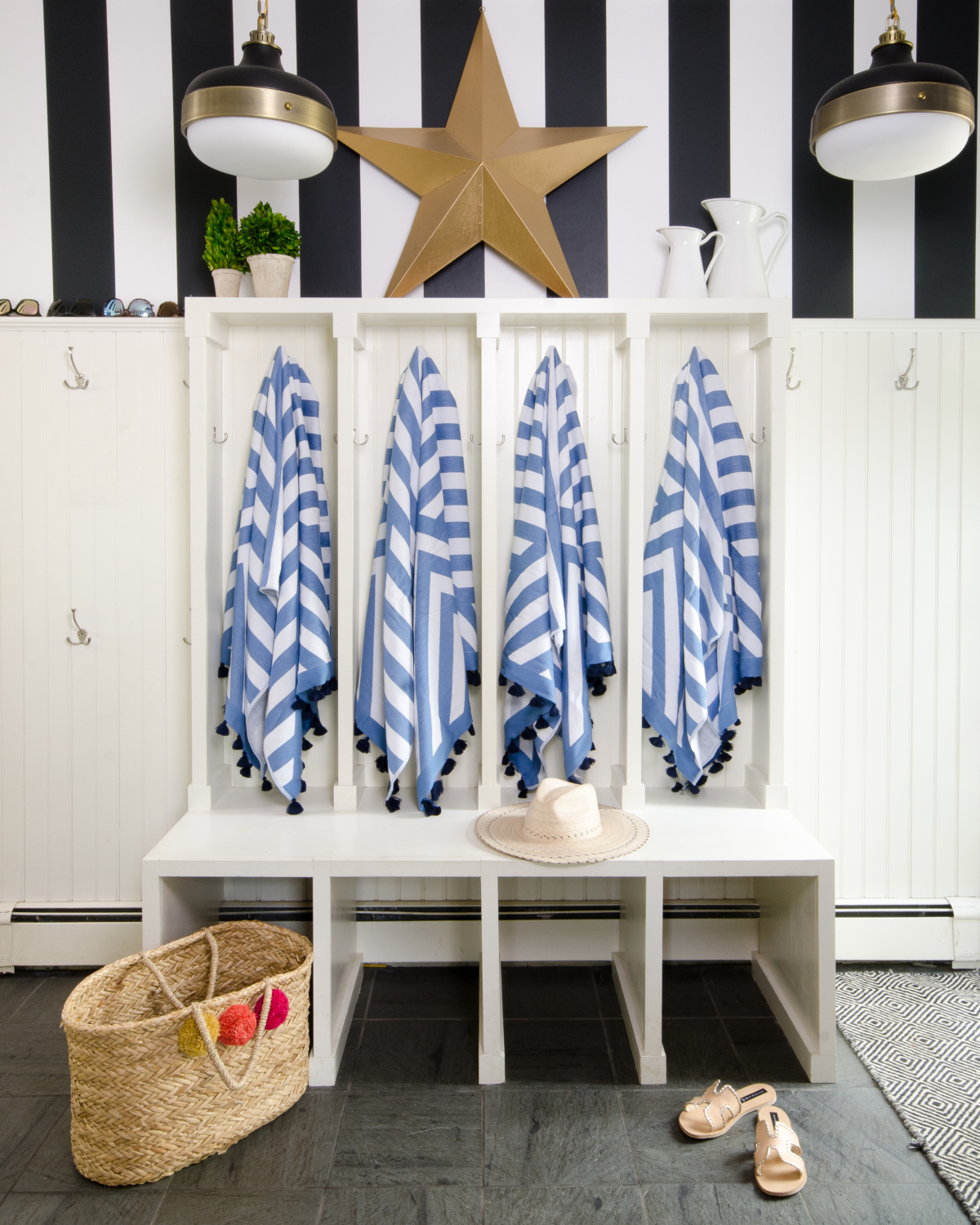 Mudroom with black and white striped wallpaper and beadboard paneling. Includes Feiss cadence pendants and features Serena and Lily Sydney beach towels.