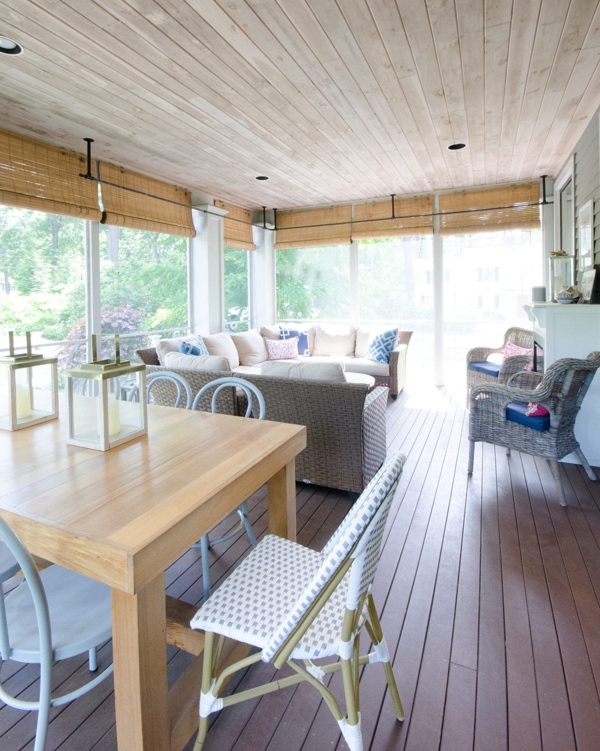 Screened porch space with dining and seating areas, a wood planked ceiling, and built in fireplace.