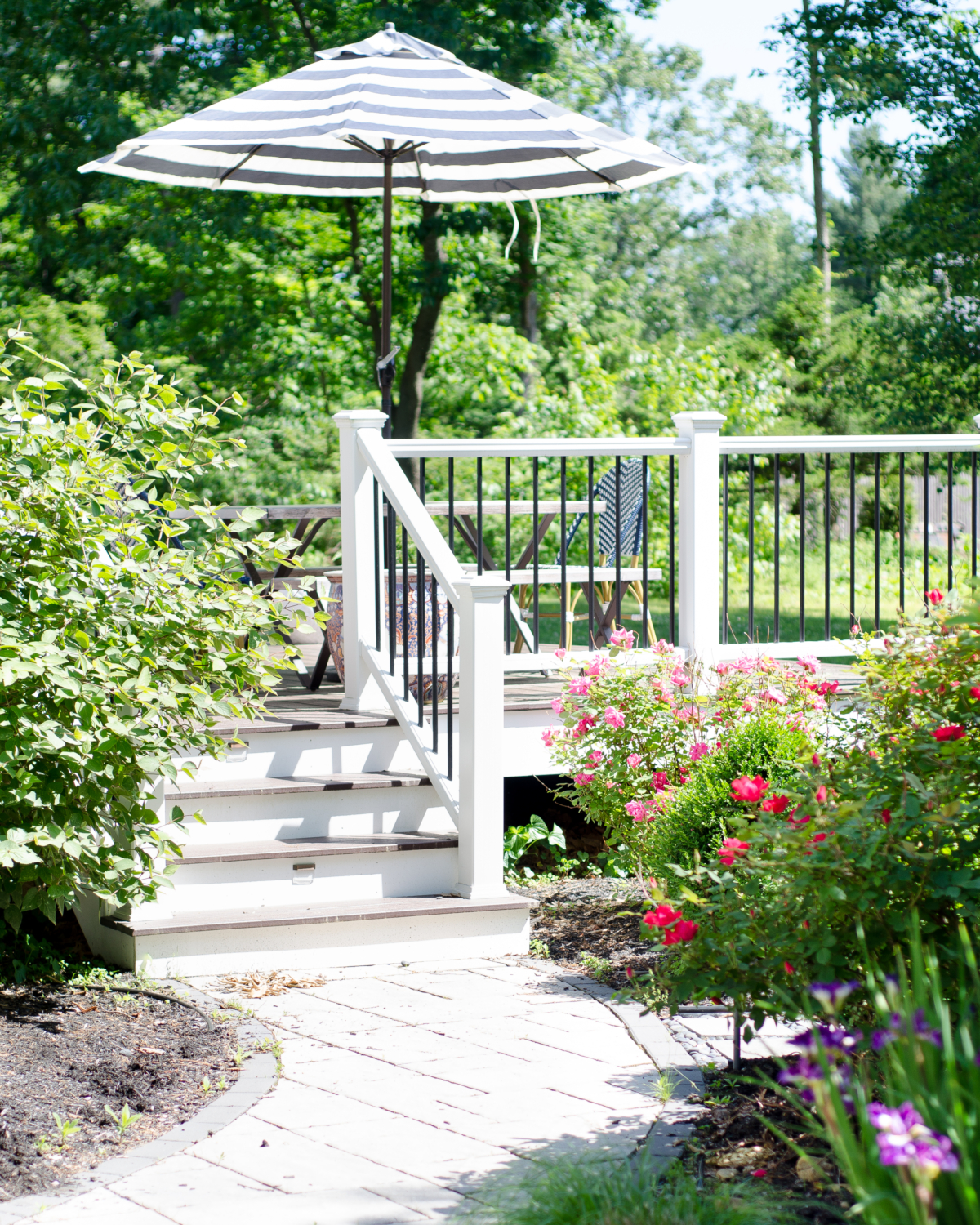 Gorgeous deck space with lush plantings, dining space, and lounge chairs.