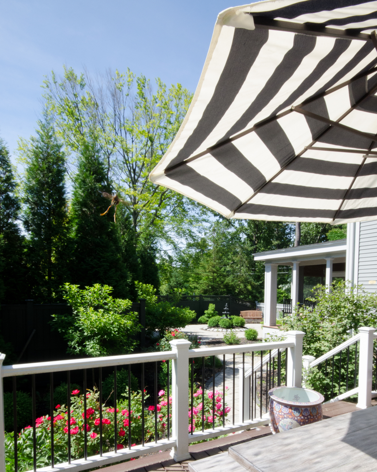 Gorgeous deck and patio spaces with lush plantings, dining space, lounge chairs, and a centerpiece fountain.