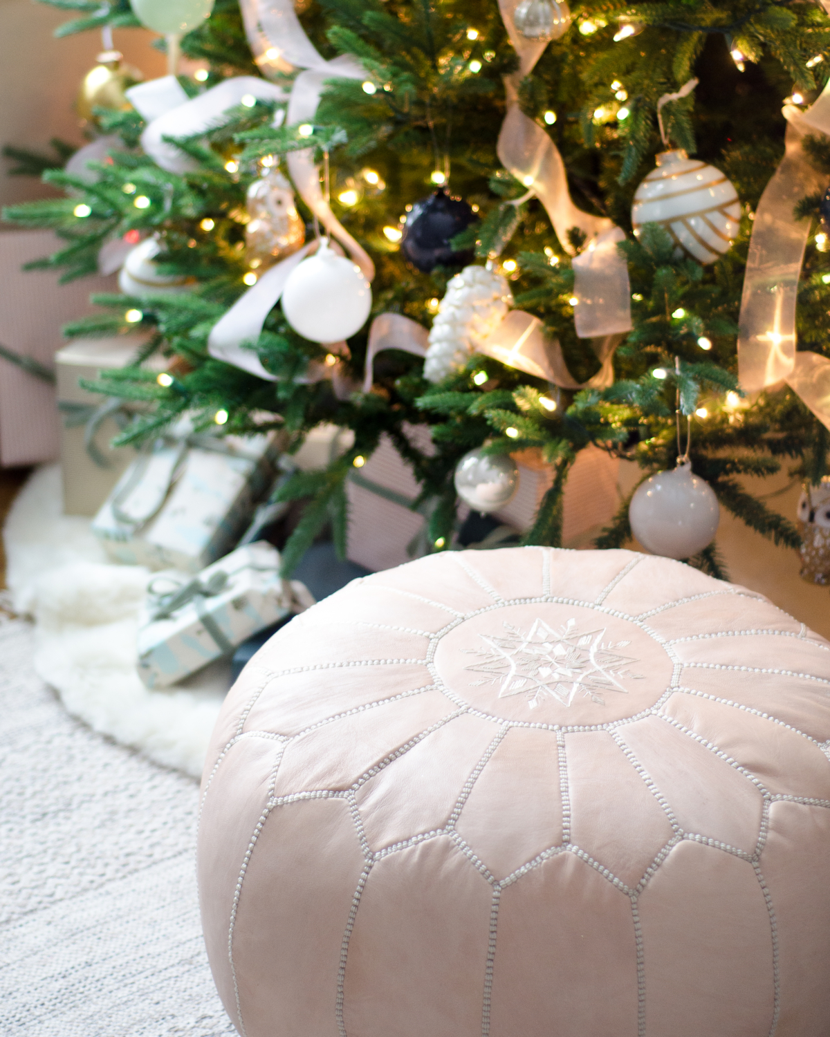 Christmas tree decorated in blush pink, deep teal, white, gold, and navy blue.