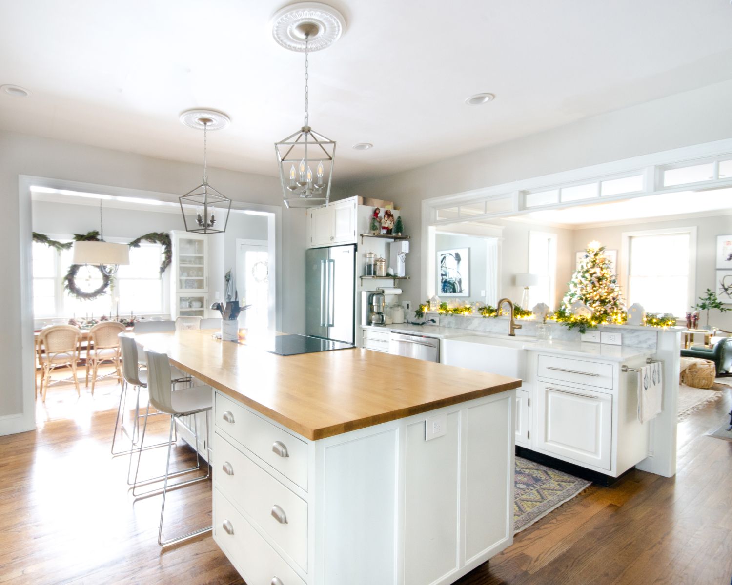Christmas kitchen with white cabinets and butcher block counter on the island.