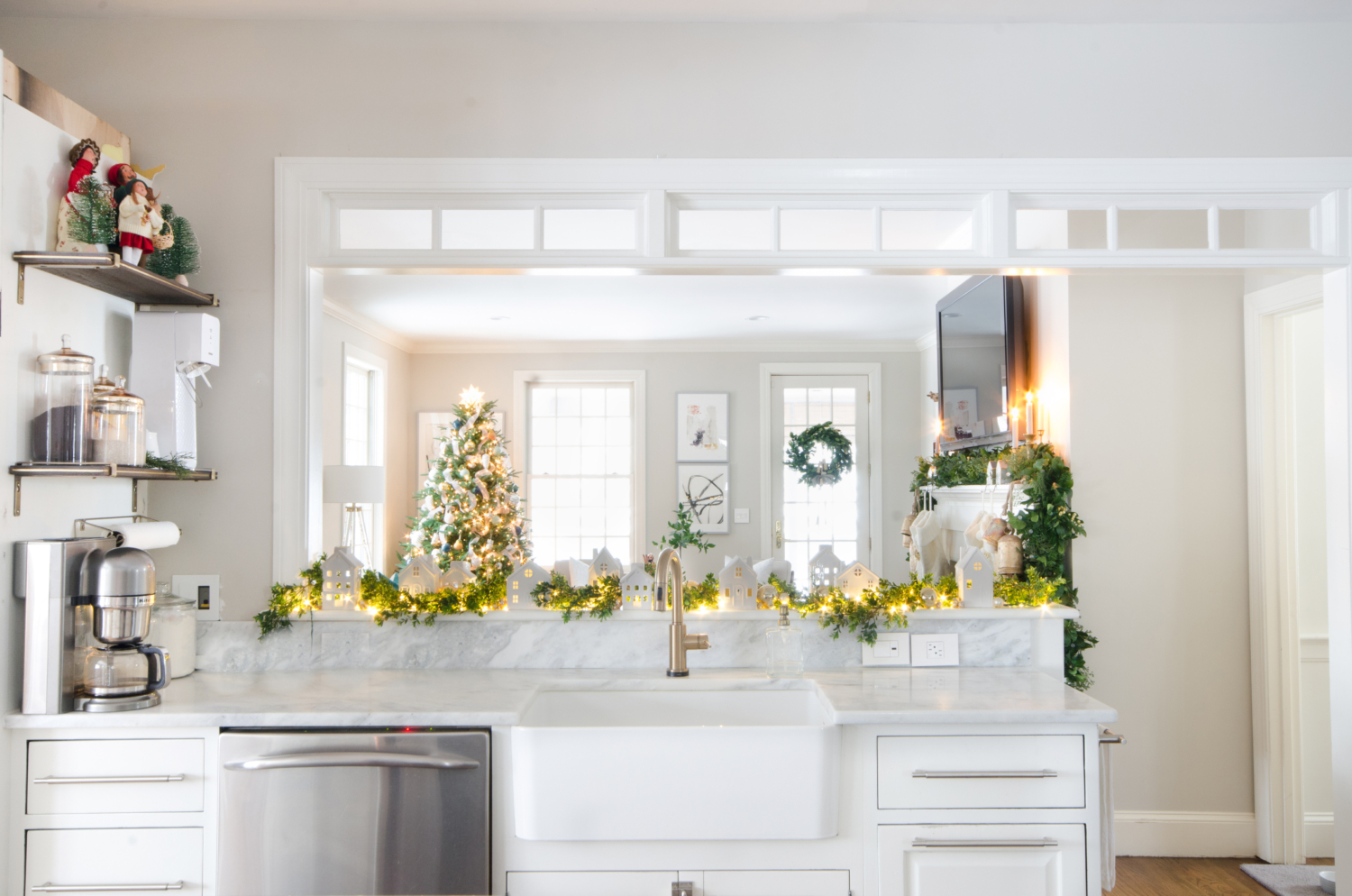 Christmas kitchen with white ceramic houses, boxwood garland, and twinkle lights.