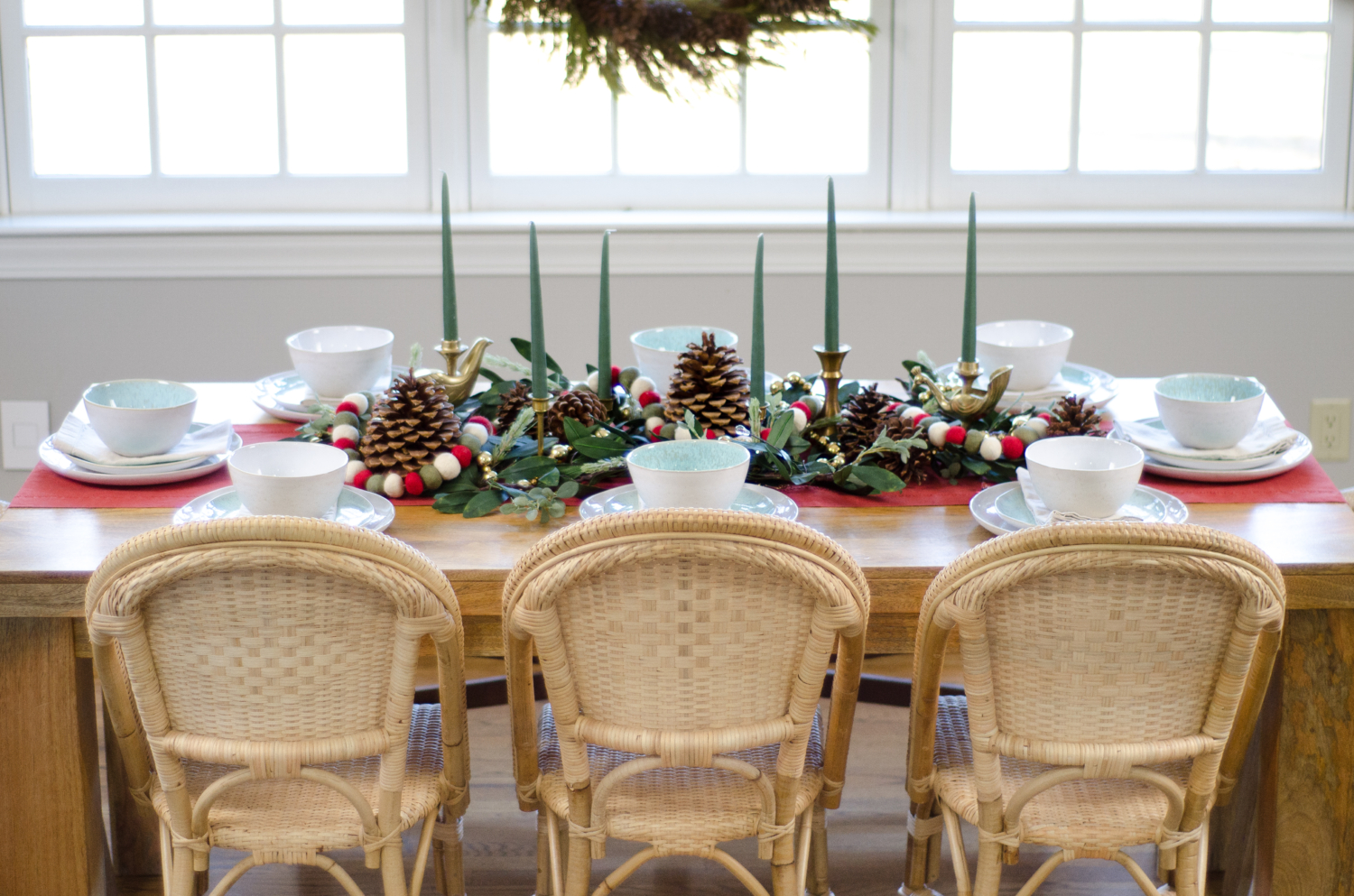 Neutral Christmas table setting in the kitchen featuring preserved cedar garland and a wreath, sunwashed Riviera side chairs, and woven rope armchairs.