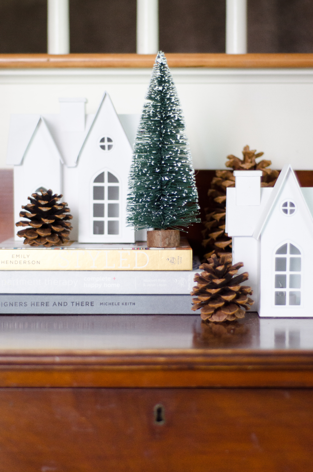 Neutral Christmas vignette with white village houses, bottle brush trees, and pinecones.