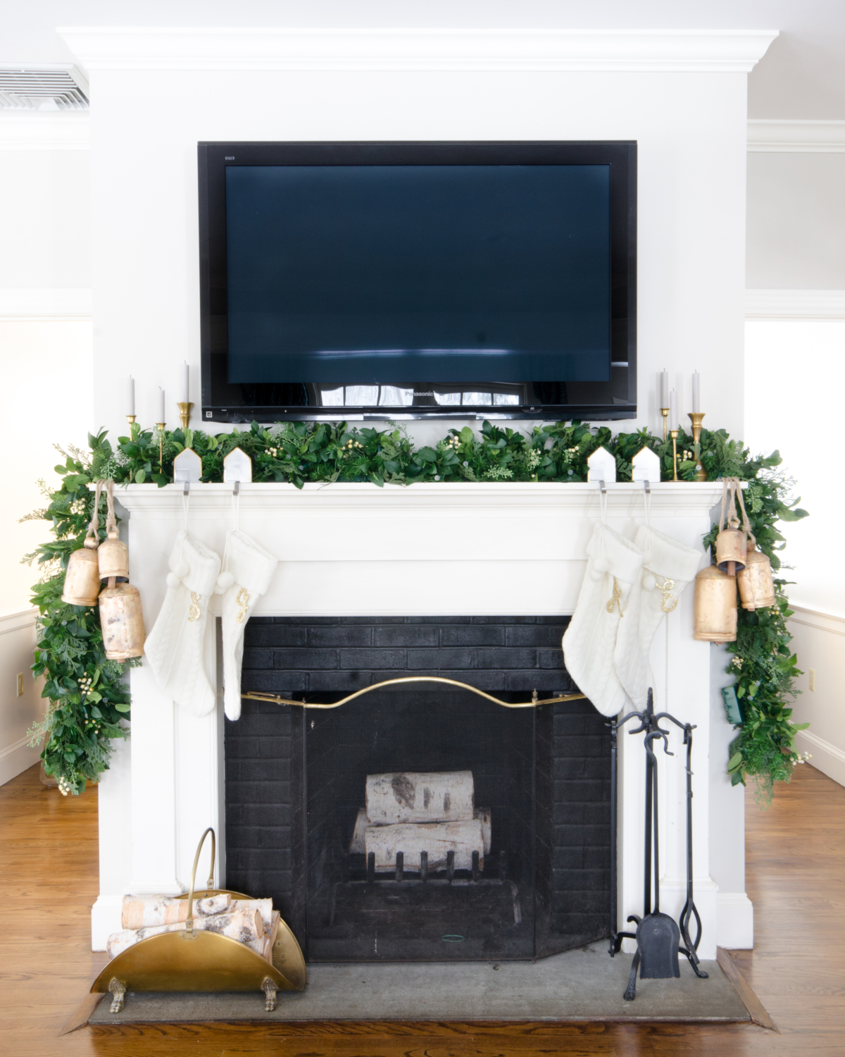 Christmas mantle with a lush garland, white cable knit stockings, gold bells, and vintage brass tulip candlesticks.