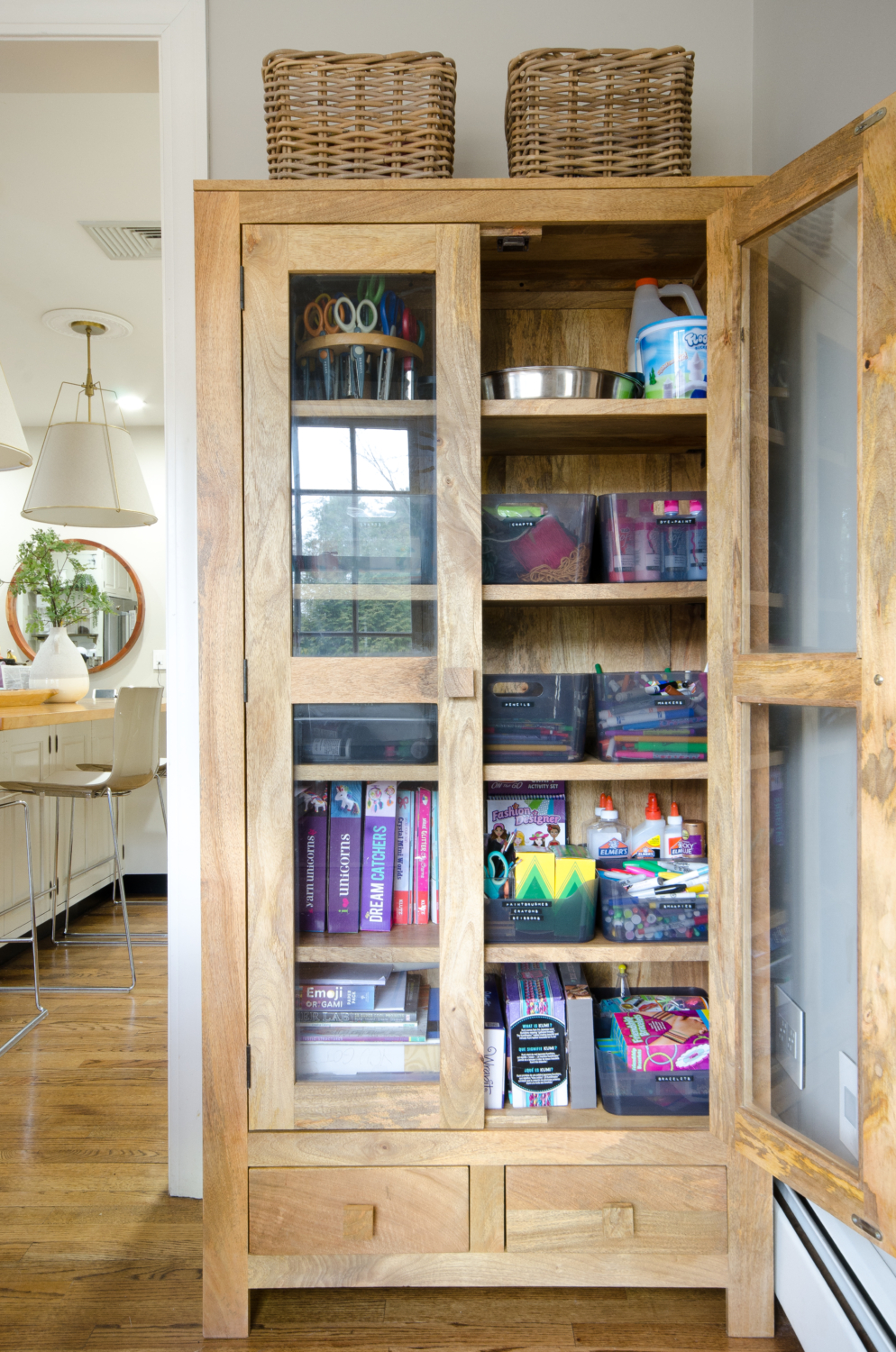 Glass front storage cabinet used to organize kids' art supplies